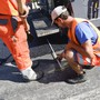 Bauarbeiter arbeiten bei grösster Hitze am Deckbelag