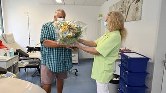 Andreas Schlup erhält zum Jubiläum seiner 100. Blutspende einen Blumenstrauss von Judith Leuenberger, medizinische Fachfrau.