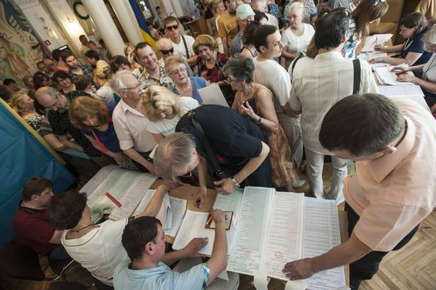 Ukrainer stehen bei einem Wahllokal an.
