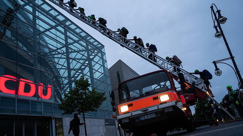 dpatopbilder - Greenpeace-Aktivisten klettern am frühen Morgen auf das Dach der CDU-Parteizentrale. Die Organisation demonstriert mit der Aktion für den Kohleausstieg. Foto: Christophe Gateau/dpa
