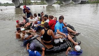 Hoffnung auf ein besseres Leben: Tausende Migranten aus Honduras versuchen via Mexiko in die USA zu gelangen. Viele versuchen, den Grenzpolizisten auf der Brücke mit dem Weg durchs Wasser auszuweichen.