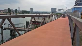 Der Steg kostet 35'000 Euro und ist 3,50 bis 4 Meter breit. Im Hintergrund die Zelte der Lindan-Sanierung und das neue Hochhaus vom Campus Novartis.