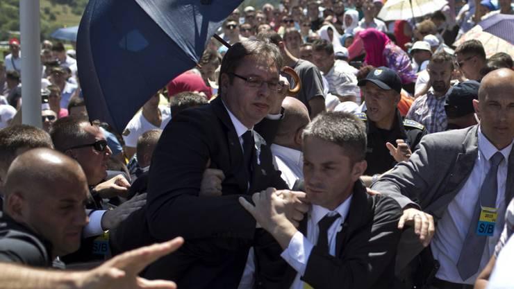 Der serbische Ministerpräsident Aleksandar Vucic (unter dem Sonnenschirm) wird abgeschirmt von seinen Leibwächtern vom Gedenkort weggeführt. Aufgebrachte Demonstranten hatten Steine nach ihm geworfen