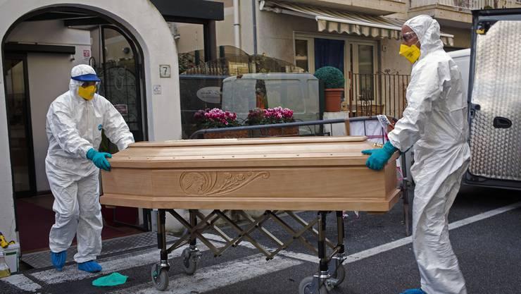 Pflegepersonal mit einem Sarg in Italien.