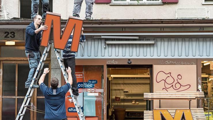 Die Migros muss sich anpassen: Arbeiter demontieren das grosse «M» auf dem Dach einer Filiale.
