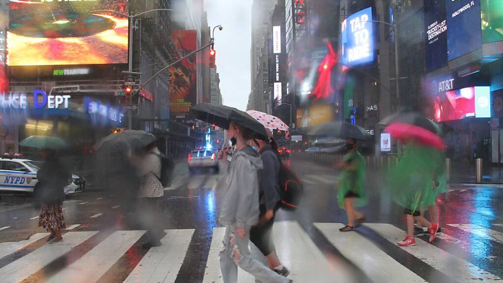 Fußgängerinnen und Fußgänger bei der Straßenüberquerung am Times Square schützen sich mit Regenschirmen vor starkem Regen. Der Tropensturm «Henri» hat in der U-Bahnstation Times Square - 42nd Street einen Wasserschaden verursacht. Foto: Niyi Fote/TheNEWS2 via ZUMA Press Wire/dpa