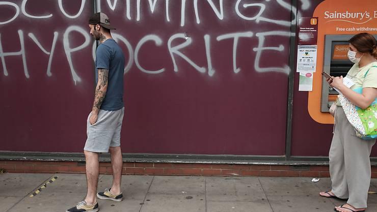 """Ein Mann und eine Frau mit Mundschutz gehen an einem Graffiti vorbei, das an die Wand eines Supermarkts in der Nähe des Hauses von Regierungsberater Cummings gesprüht wurde. Das Graffiti mit der Aufschrift """"Scummings Hypocrite"""" (Heuchler)  kritisiert Cummings, der trotz des Lockdowns mehr als 400 Kilometer zu seinen Eltern gereist ist, als er an Covid-19-Symptomen litt. Foto: Yui Mok/PA Media/dpa"""