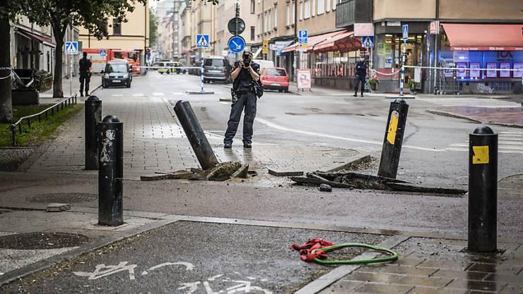 In Stockholm ist ein Lastwagen ohne anzuhalten in ein Taxi gerast - ein Polizeifotograf macht Bilder vom Unfallort.