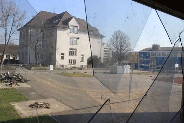 Blick durch zerborstenes Fenster auf den Pausenplatz