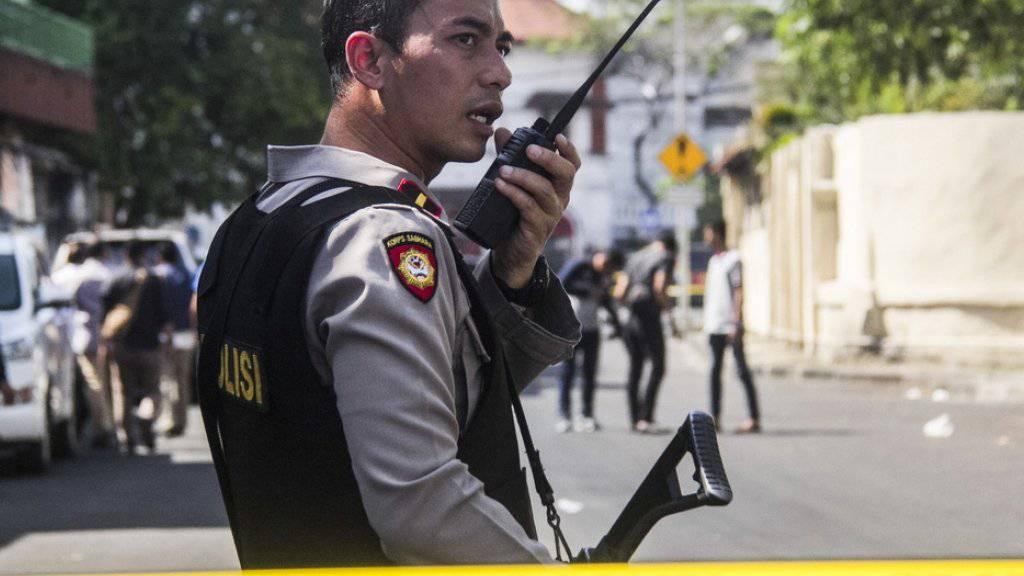Ein indonesischer Polizist sichert den Tatort ab. Bei dem Selbstmordanschlag in der Grossstadt Surabaya wurden erneut Kinder eingesetzt.