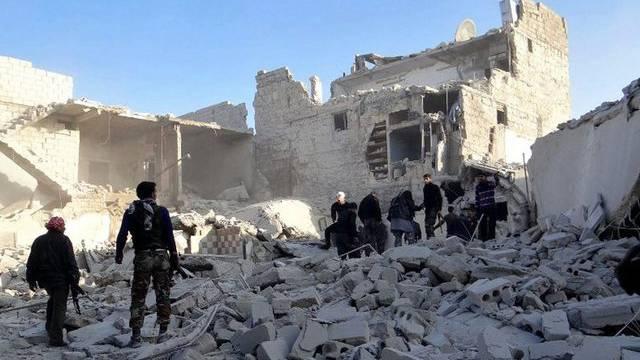Syrische Rebellen stehen auf den Trümmern eines zerbombten Hauses bei Aleppo (Archiv)