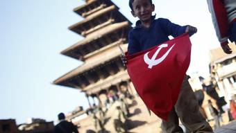 Knabe mit kommunistischer Flagge in Nepal, wo die ehemaligen Rebellen Parteitag halten (Symbolbild)