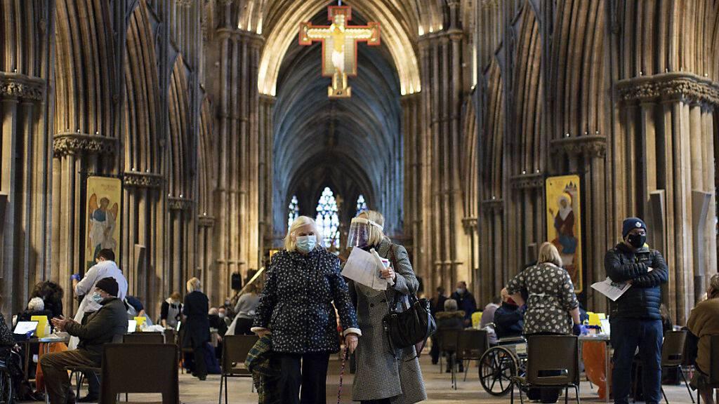 Audrey Elson (l, 84) verlässt mit ihrer Tochter die Lichfield Kathedrale, nachdem sie dort mit dem Corona-Impfstoff der Universität Oxford und des Konzerns Astrazeneca geimpft wurde. Foto: Jacob King/PA/AP/dpa