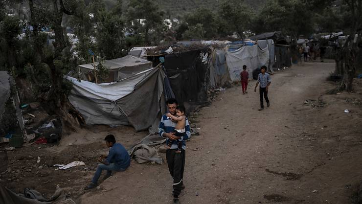 Ein Geflüchteter läuft mit einem Kind durch ein Übergangslager neben dem Flüchtlingslager Camp Moria. Foto: Angelos Tzortzinis/DPA