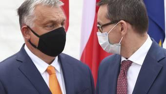ARCHIV - Mateusz Morawiecki (r), Premierminister von Polen, trägt einen Mundschutz und begrüßt Viktor Orban, Premierminister von Ungarn, ebenfalls mit Mundschutz, zum Treffen der Premierminister der Visegrad-Staaten. Foto: Czarek Sokolowski/AP/dpa