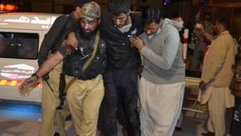 Rettungskräfte bringen einen Verletzten in Sicherheit nach dem Überfall auf eine Polizeischule in Pakistan.