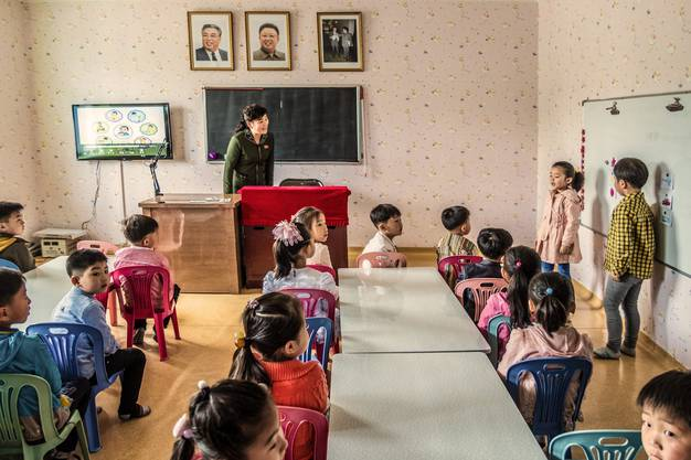 """Unterricht an der Kim Jong Suk Middle School No. 1 in Pyongsong, der zweitgrössten Stadt des Landes. Wenn man genau hinschaut, sieht man Post-it's mit Panzern auf der weissen Tafel – der """"Geschichtsunterricht"""" beginnt früh!"""