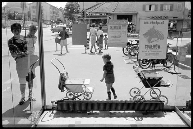 Familien beim Samstagseinkauf an der Landstrasse in Wettingen. Fotografiert durch Schaufenster, 1968.