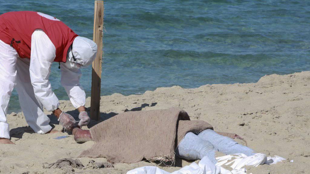 Ein libyscher Retter kümmert sich um eine der bisher 67 aus dem Mittelmeer geborgenen Leichen des Bootsunglücks vor der Hafenstadt Al-Chums.