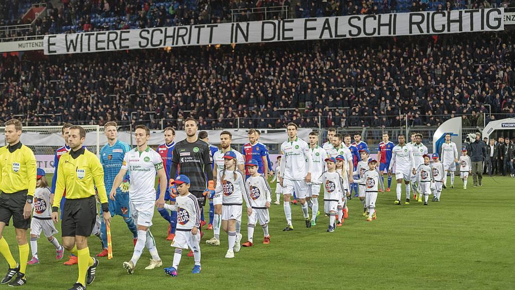 Die Fans der Muttenzer Kurve begruessen die Mannschaften mit einem Transparent mit der Aufschrift «E witere Schritt in die falschi Richtig». (© Keystone)