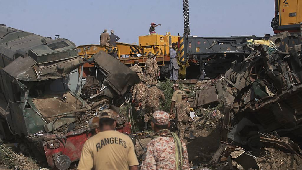 Soldaten kommen an, um die Strecke an der Stelle einer Zugkollision im Bezirk Ghotki im Süden Pakistans zu räumen. Foto: Fareed Khan/AP/dpa