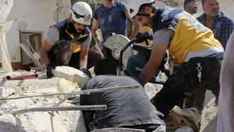 Rettungskräfte der Organisation Weisshelme suchen unter den Trümmern eines durch Luftangriffe zerstörten Gebäudes in Idlib nach Opfern.