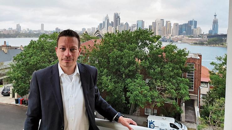 Raphael Schmid auf dem Balkon seiner Wohnung mit Sicht auf den Hafen und das Sydney Opera House.