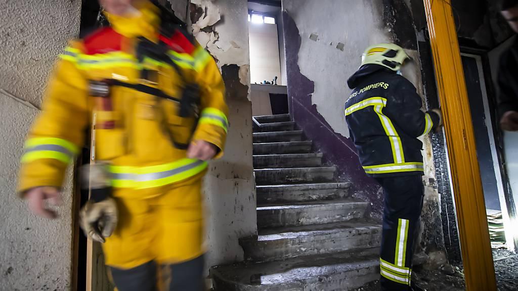 Feuerwehrleute an der Arbeit im vom Brand beschädigten Wohnblock in Genf.