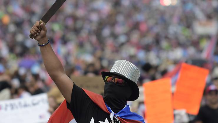 Ein Demonstrant hält eine Machete in die Höhe während eines Marsches auf der Autobahn bei San Juan.