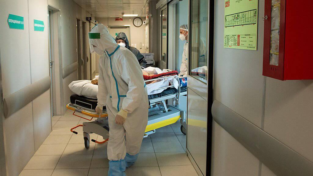 ARCHIV - Medizinische Mitarbeiter in Schutzkleidung schieben das Bett eines Corona-Patienten im städtischen Krankenhaus Nr. 52 in Moskau. (Archivbild) Foto: Denis Grishkin/Moscow News Agency/AP/dpa