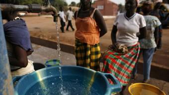 Frauen in Guinea erhalten sauberes Wasser von einem Hilfswerk. (Archiv)