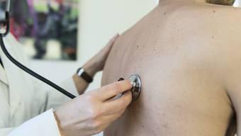 Ein Arzt untersucht einen Patienten: Solche ambulante Behandlungen liessen die Gesundheitskosten steigen, schreibt der Krankenkassendachverband Santésuisse.