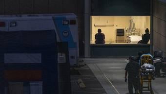 """Ein Rettungsdienst bringt einen Patienten zu dem staatlichen Krankenhaus """"Los Angeles County + USC Medical Center"""". Foto: Damian Dovarganes/AP/dpa"""