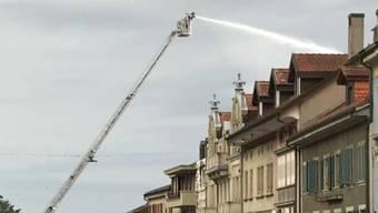 Ein Feuerwehrmann bekämpft von einer Drehleiter aus den Dachstockbrand.