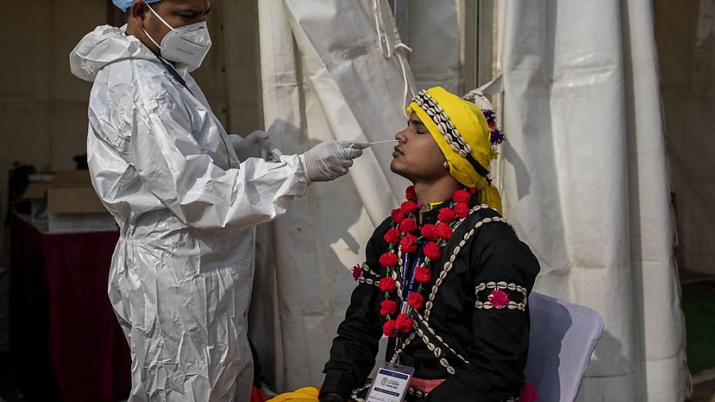 ARCHIV - Ein Mitarbeiter des Gesundheitswesen in Indien entnimmt einem Mann einen Abstrich für einen Corona-Test. Foto: Altaf Qadri/AP/dpa
