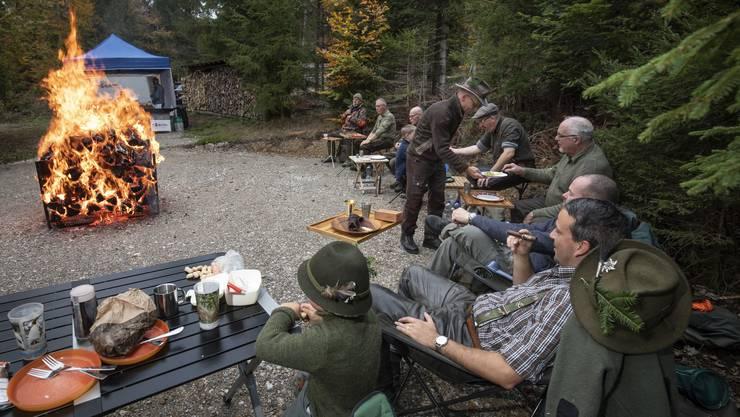 «Ein wichtiger Aspekt der Jagd ist die Kameradschaft», erklärt Stephan Glättli (rechts mit Zigarre). So sitzen die Jäger am Ende des Jagdtages zusammen ums Feuer — bei Speis und Trank.