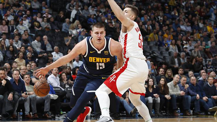 Denvers Center Nikola Jokic (links) zieht an Houstons Center Isaiah Hartenstein vorbei zum Korb
