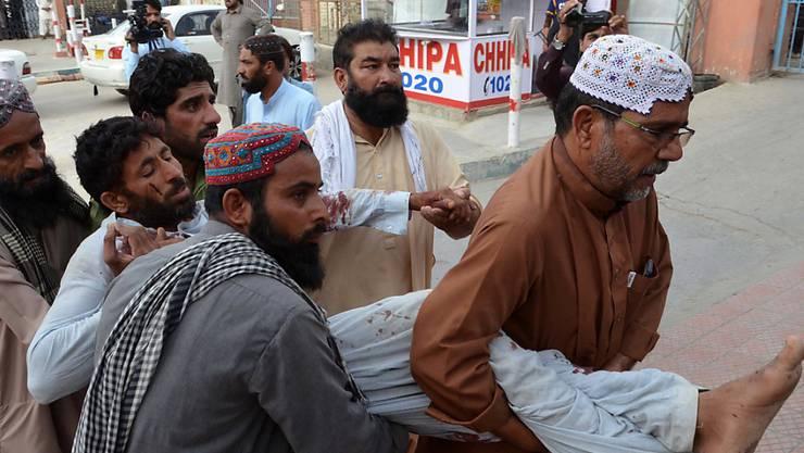 Helfer bringen ein verletztes Opfer des Anschlages in Pakistan in Sicherheit.
