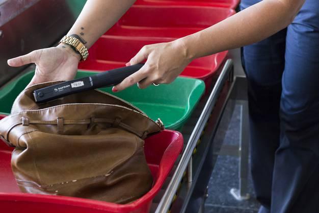 Eine Mitarbeiterin der Flughafenpolizei macht eine gestellte Stichproben-Kontrolle der Handtasche einer Passagierin