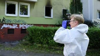 Ein Gerichtsmediziner fotografiert die ausgebrannte Wohnung in Dortmund