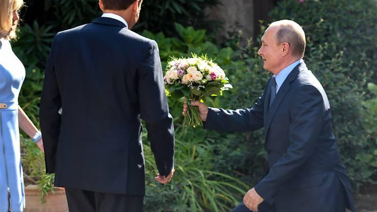Blumen aus der Hand des russischen Präsidenten Wladimir Putin für die Frau des französischen Präsidenten, Brigitte Macron.