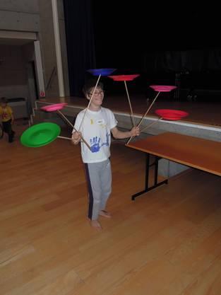 Alle bewundern Adam, der auf sechs Holzstäben, sechs sich drehende bunte Teller, balancieren kann.
