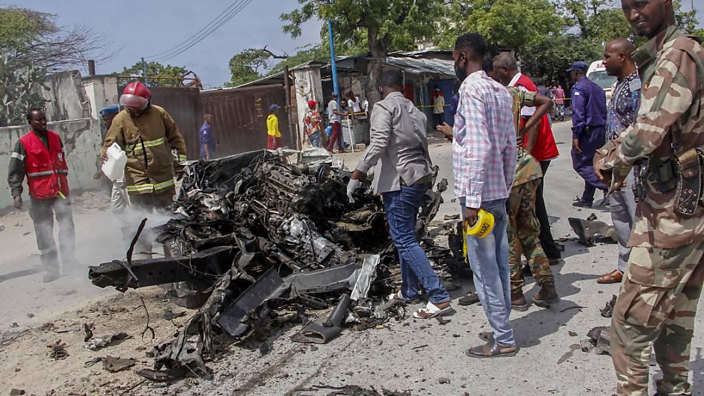 Sicherheitskräfte und Zivilisten stehen in der Nähe eines Autowracks nach einem Anschlag auf den Polizeichef von Mogadischu. Foto: Farah Abdi Warsameh/AP/dpa