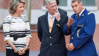 Ein Polizeioffizier redet mit dem Königspaar in Charleroi über den Tathergang.