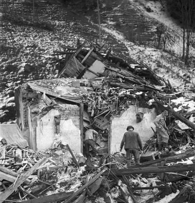 Helfer durchsuchen ein durch die Explosion komplett zerstörtes Gebäude in Mitholz im Kandertal, aufgenommen im Dezember 1947. In der Nacht auf den 20. Dezember 1947 vernichteten drei gewaltige Explosionen rund die Hälfte der Munition, die in einem Depot oberhalb von Mitholz-Blausee eingelagert waren.