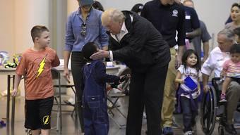 """Aufmunterung für die Opfer von Sturm """"Harvey"""": Das Präsidentenpaar betüdelt im NRC Center Kinder und gibt Essen aus."""