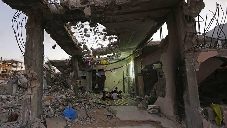 Kinder essen in den Trümmern ihres Hauses, das im Krieg 2014 zerstört wurde