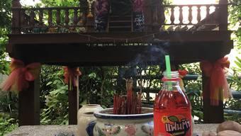 Flaschen mit roter Erdbeer-Fanta sind vor einem Schrein zu sehen. In Thailand sind die Geister wahre Naschkatzen. Um sich ihre Gunst zu sichern, werden sie von Gläubigen mit allerlei Leckereien versorgt - speziell mit roter Erdbeer-Fanta. Was hat es mit den kuriosen Opfergaben auf sich? (zu dpa: «Rote Limo für die Geister») Foto: Kaweewit Kaewjinda/dpa