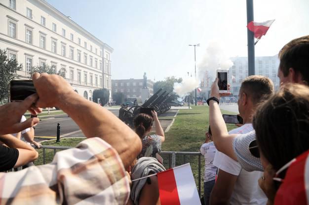 Besucherinnen und Besucher beobachten und filmen die Zeremonie auf dem Pilsudski-Platz.