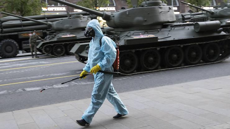 dpatopbilder - Ein städtischer Angestellter, der einen Spezialanzug zum Schutz gegen das Coronavirus trägt, desinfiziert einen Bereich, während sich sowjetische Panzer T-34 aus dem Zweiten Weltkrieg auf eine Probe für die Foto: Alexander Zemlianichenko/AP/dpa